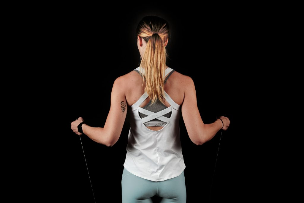 woman with back turned, using a resistance band for exercise